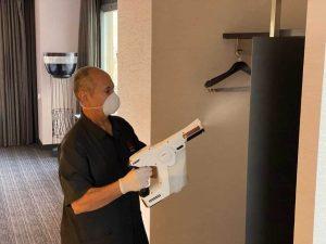camarero de hotel con máquina sanitizadora